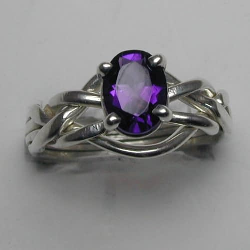 A four band puzzle ring with an amethyst stone
